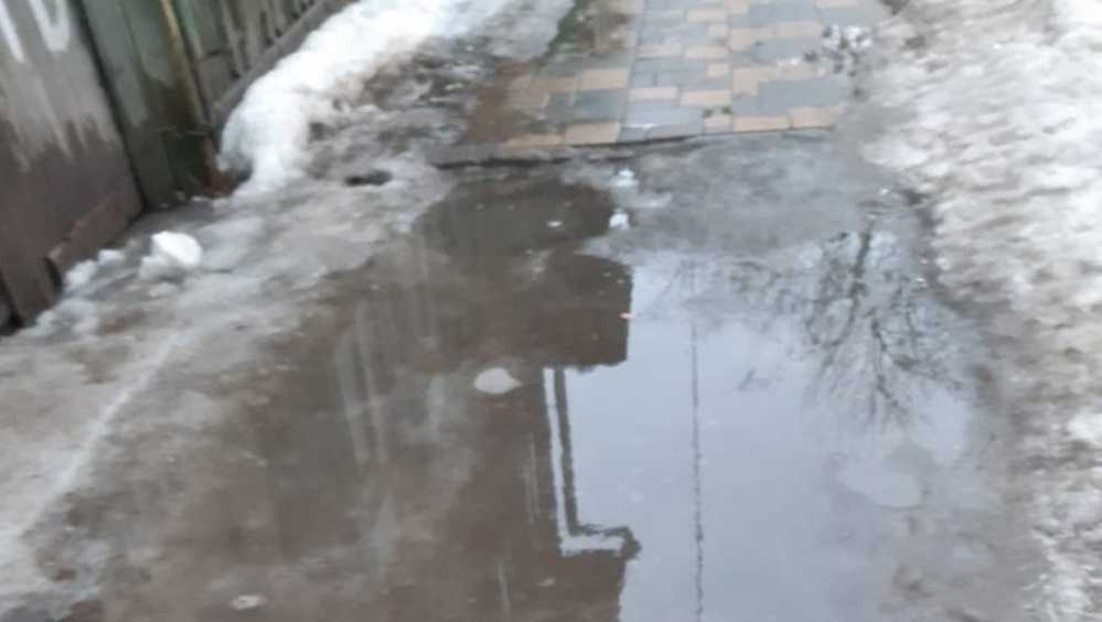 Жительница Брянска на обледенелом тротуаре поскользнулась и упала в лужу